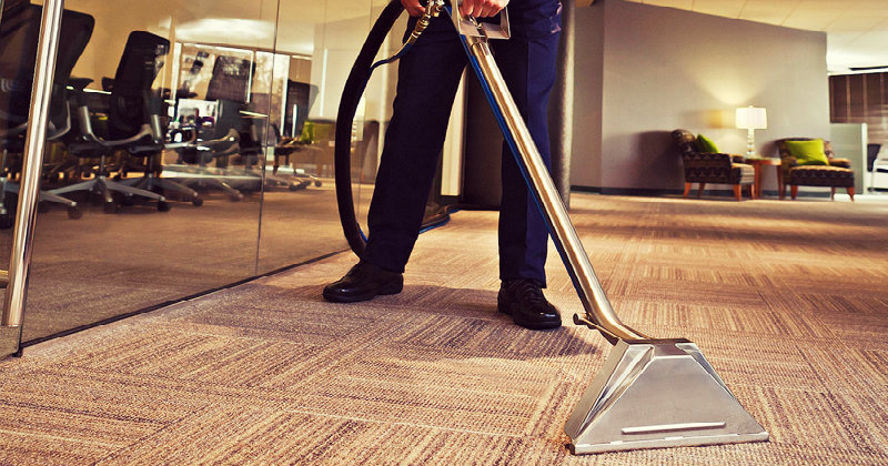 cropped image of a man vacuuming office carpet