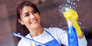 smiling young woman spraying solution on glass and wiping with squeegee