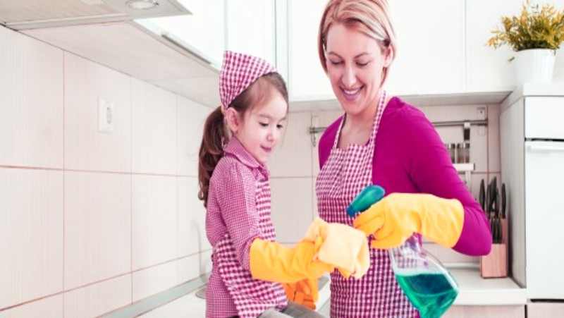 a mother and a daughter with orange gloves making their kitchen spotless