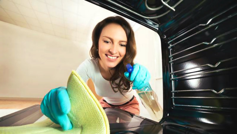 happy woman wiping oven surface