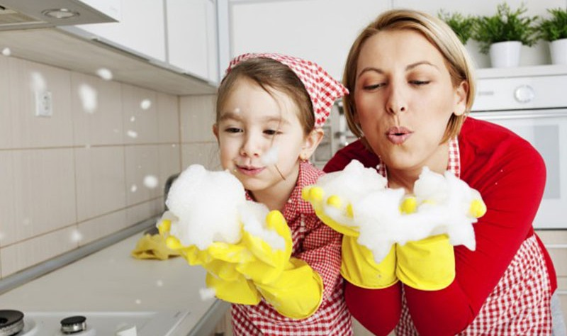 happy mother and daughter playing with soap bubbles