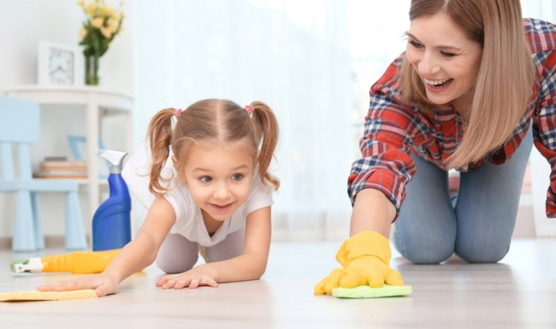 a mother is moping the floor with her daughter