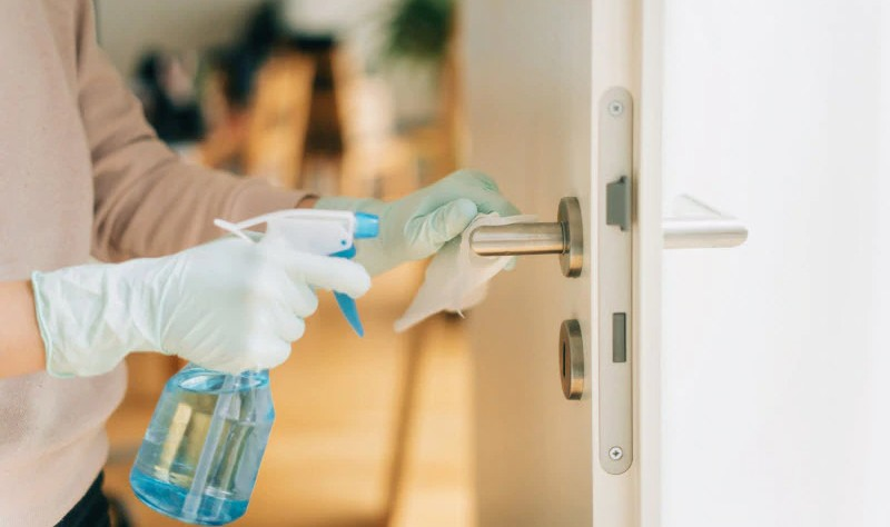 cropped picture of a man spraying solution on a door knob