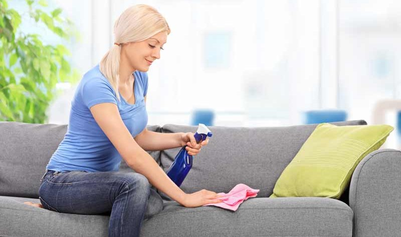 beautiful woman sitting on a couch and wiping it with a cloth