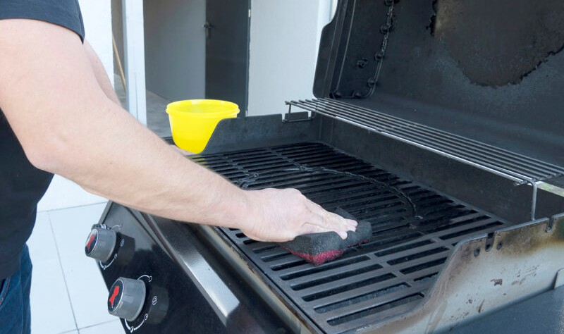 young man wiping grill grates with a sponge