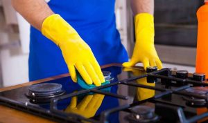 cropped image of a man wiping a gas stove with a rag