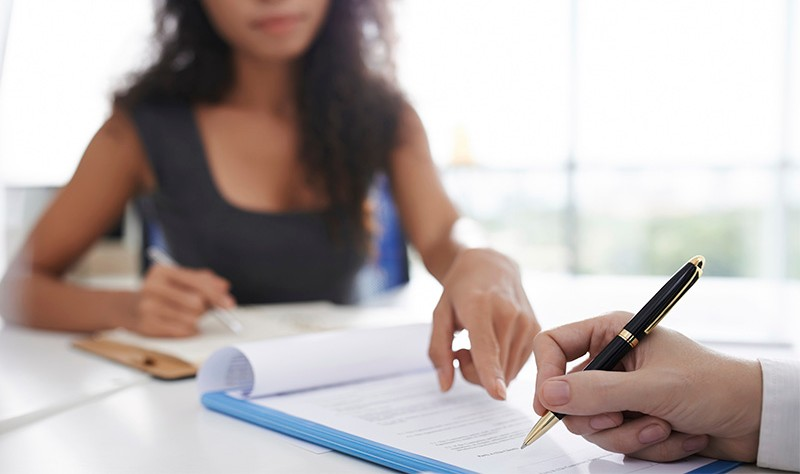 cropped image of a woman asking for signature from a man