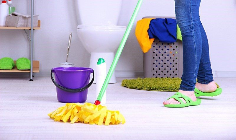 cropped image of a woman wiping the bathroom floor with a wiper