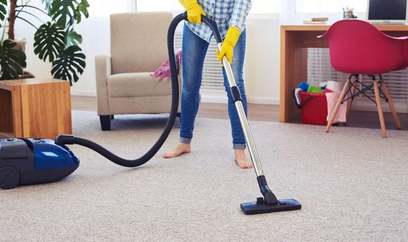 cropped image of a young woman vacuuming a carpet