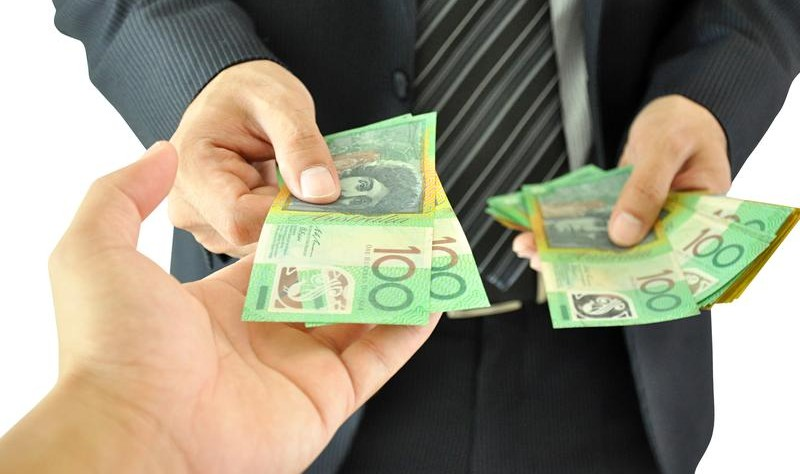 cropped image of two person exchanging Australian currency