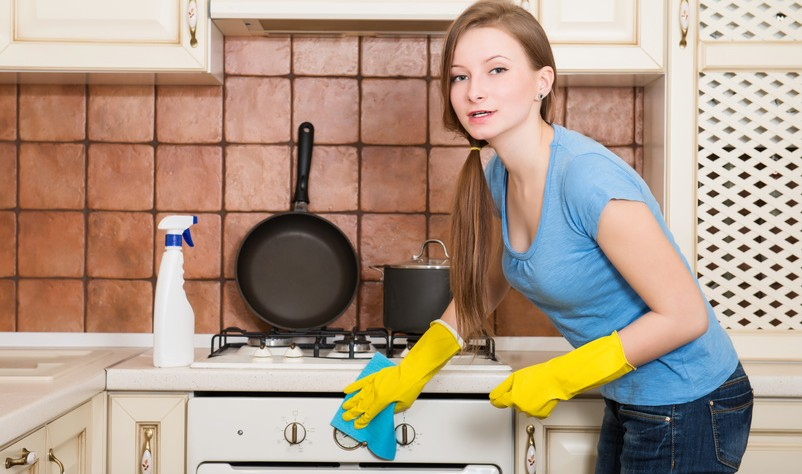 Beautiful young woman wiping a gas stove with a cloth rag