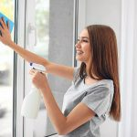 beautiful young woman wiping window glass with a cloth rag