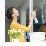 young woman spraying something on a window glass