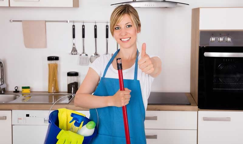 young woman with a blue apron standing in a kitchen with a bucket and a wiper