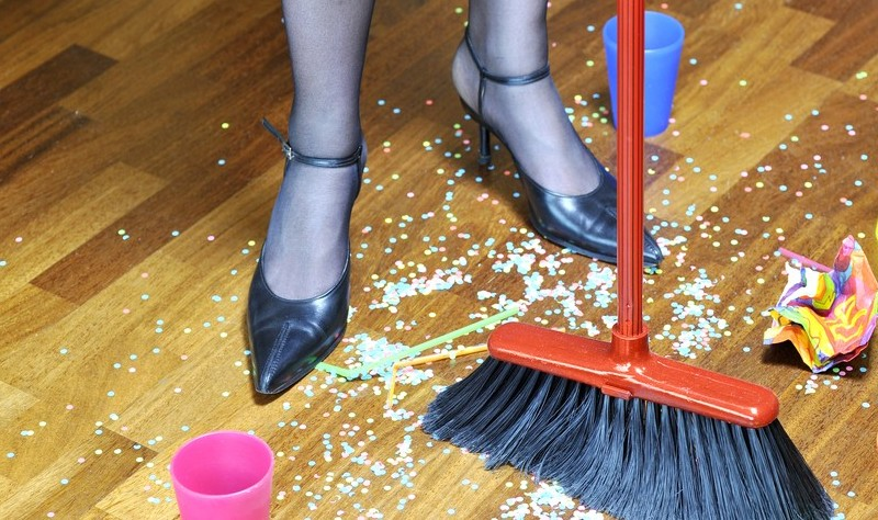 cropped picture of a woman sweeping the floor