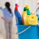 bucket full of chemical bottles and at back woman wiping a surface
