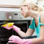 Young woman wiping a oven with a cloth rag