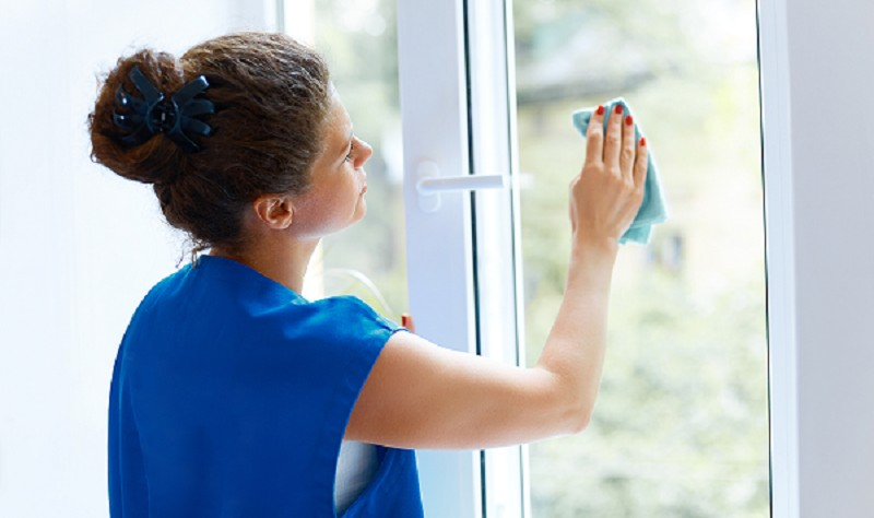 young woman wiping the window glass with a cloth