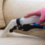 cropped picture of a person vacuuming a couch