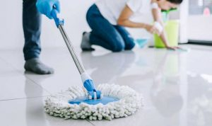 Cropped picture of a man moping the floor and a woman disinfecting the floor