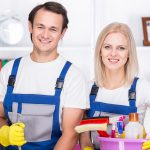 young professional couple with a basket full of chemical bottles and spray bottles