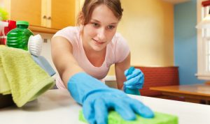 young woman moping a surface with a sponge