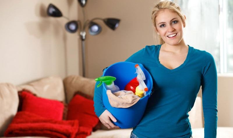 Young woman holding a bucket full of spray bottles and chemicals