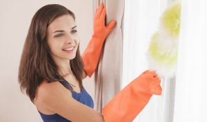 young woman dusting her house with a duster