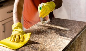 cropped picture of a person disinfecting granite surface