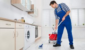 young professional wiping a kitchen floor with a wiper