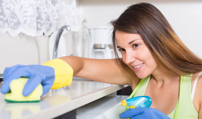young woman disinfecting a kitchen surface