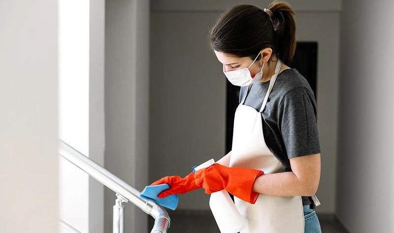 young woman wearing a mask disinfecting a surface